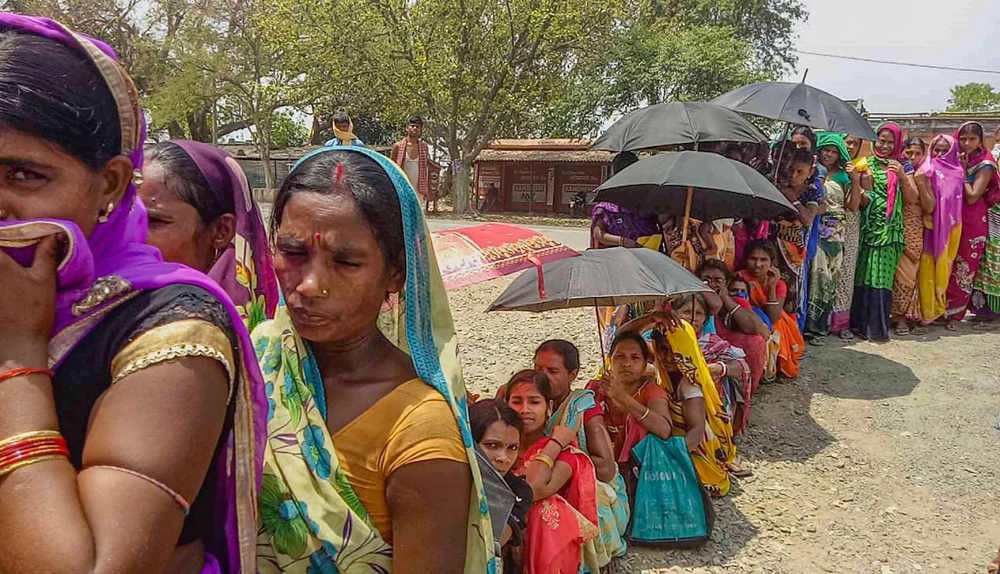 Women stand in a queue outside a bank to withdraw relief money from their Jan Dhan accounts during a nationwide lockdown in the wake of coronavirus pandemic, at Bihar Sharif in Nalanda, Friday, April 17, 2020.