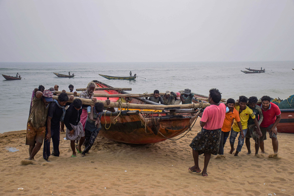 Fishermen pull a boat away from the sea following cyclone warning in Puri on Friday