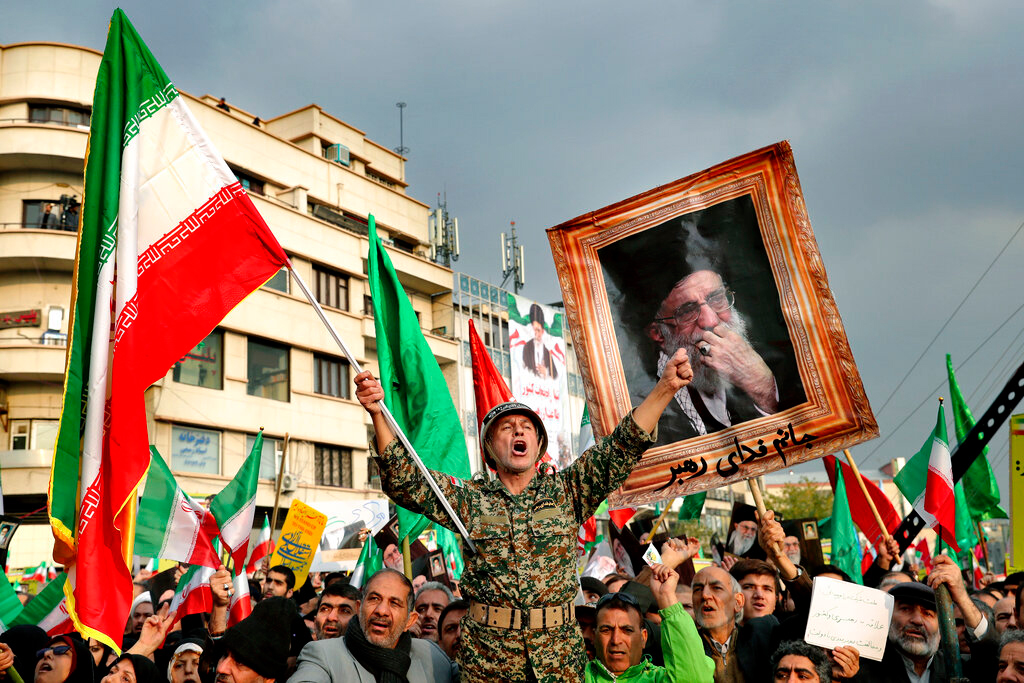 In a November 25, 2019, file photo, a demonstrator chants slogans while holding up an Iranian national flag during a pro-government rally in Tehran, Iran, denouncing violent protests over a government-imposed fuel price hike.