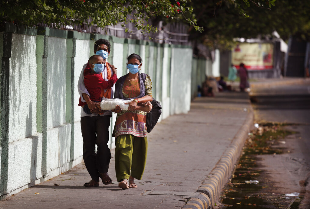 Farm laborer Ramakishan, and his wife Devshree walk carrying their son Gurudev, 11, to the All India Institute of Medical Sciences during lockdown to control the spread of the new coronavirus in New Delhi, on Monday, April 13, 2020.