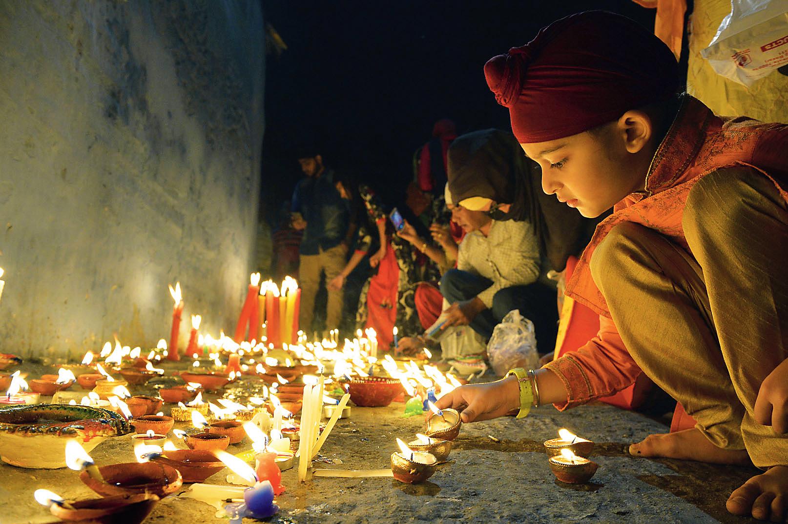 Lamps and candles being lit at Behala Gurdwara on the night of Bandi Chhor Divas.
