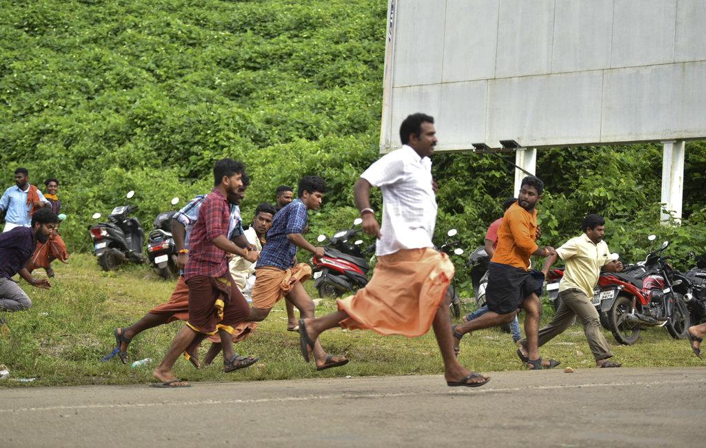 In this October 17 file photo, protesters run after being chased by police for trying to stop women of menstruating age from going to Sabarimala temple. Since the Supreme Court verdict on the issue, the Sangh Parivar has gone all out to instigate people by appealing to age-old prejudices