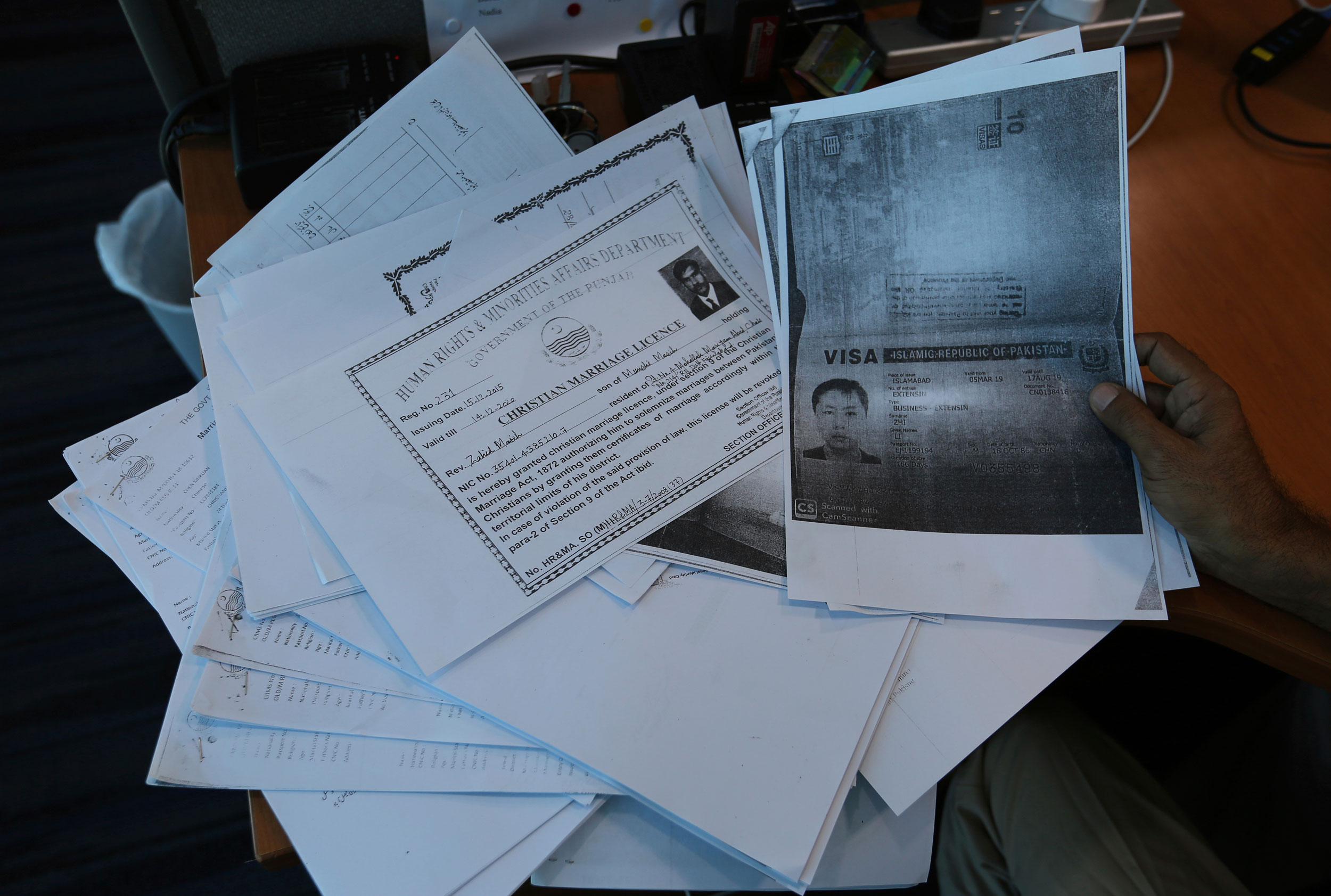 In this photo taken on May 27, 2019, a person shows photocopies of dozens of marriage contracts and other documents collected by a Pakistani security agency, in Islamabad, Pakistan.