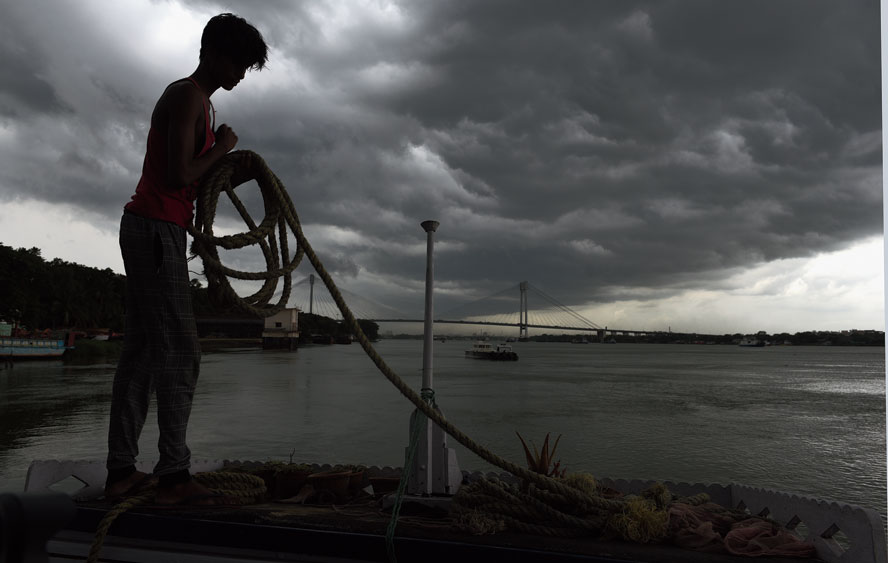 Bracing for the storm: A boy tethers a launch to the eastern bank of the Hooghly in Babughat, with dark clouds looming overhead, around 2.30pm on Tuesday.