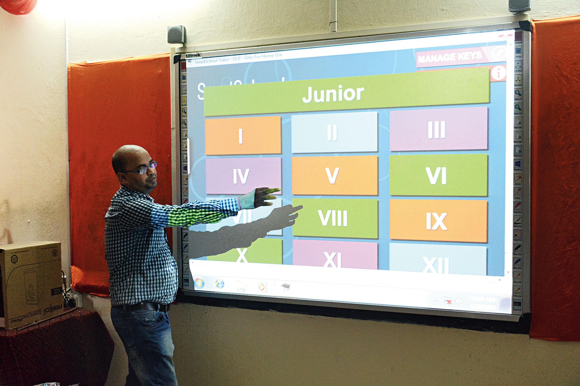 A teacher shows how the digital board works at Utkramit Madhya Vidyalaya at Bhatia Basti in Kadma, Jamshedpur, on Thursday.