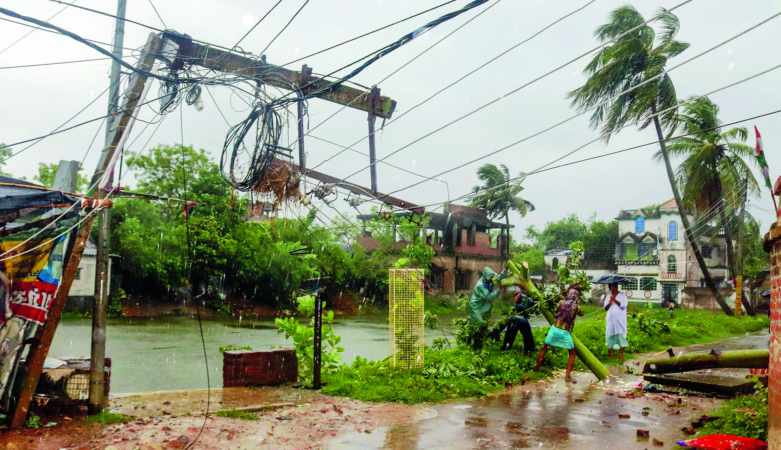 Workers try to restore a power line in Burdwan after a tree fell on it during the cyclone on Wednesday.
