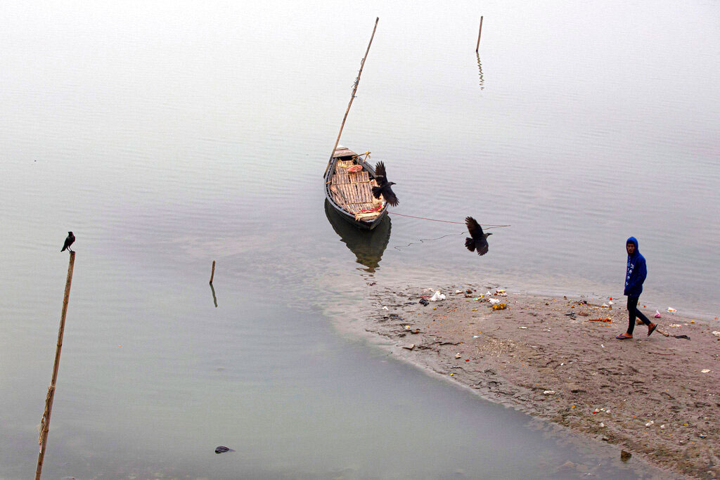 Birds fly over an anchored boat in the river Brahmaputra on a cold winter morning in Guwahati on January 3, 2020.