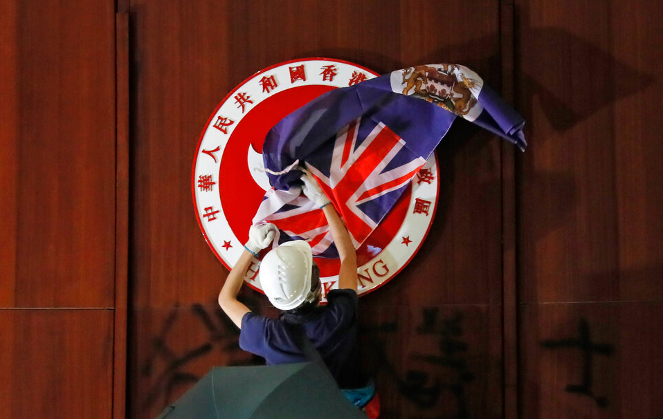 A protester attempts to cover the Hong Kong emblem with a British colonial flag in the Legislative Council building on Monday.