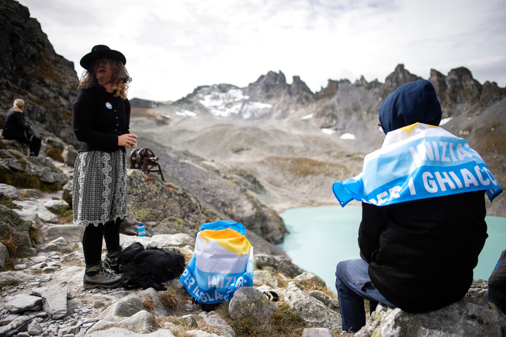 A climate change activist wears a mourning veil on her way to a ceremony to commemorate the 'dying' glacier of Pizol mountain in Wangs, Switzerland, on Sunday