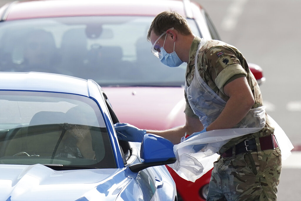 A NHS (National Health Service) worker is tested for Covid-19 by a soldier at a drive-through testing centre, in Manchester, northern England, Thursday, April 9, 2020.