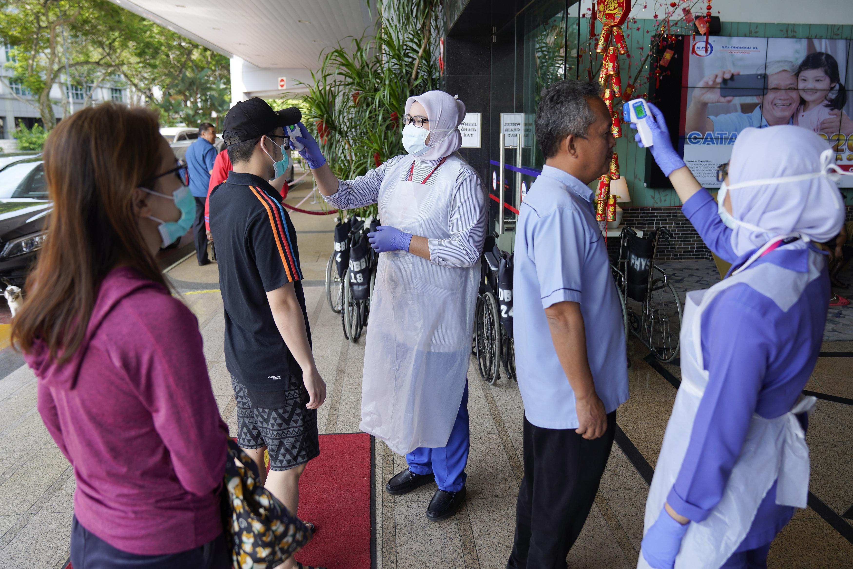 Nurses check the temperatures of visitors as part of the coronavirus screening procedure at a hospital in Kuala Lumpur, Malaysia