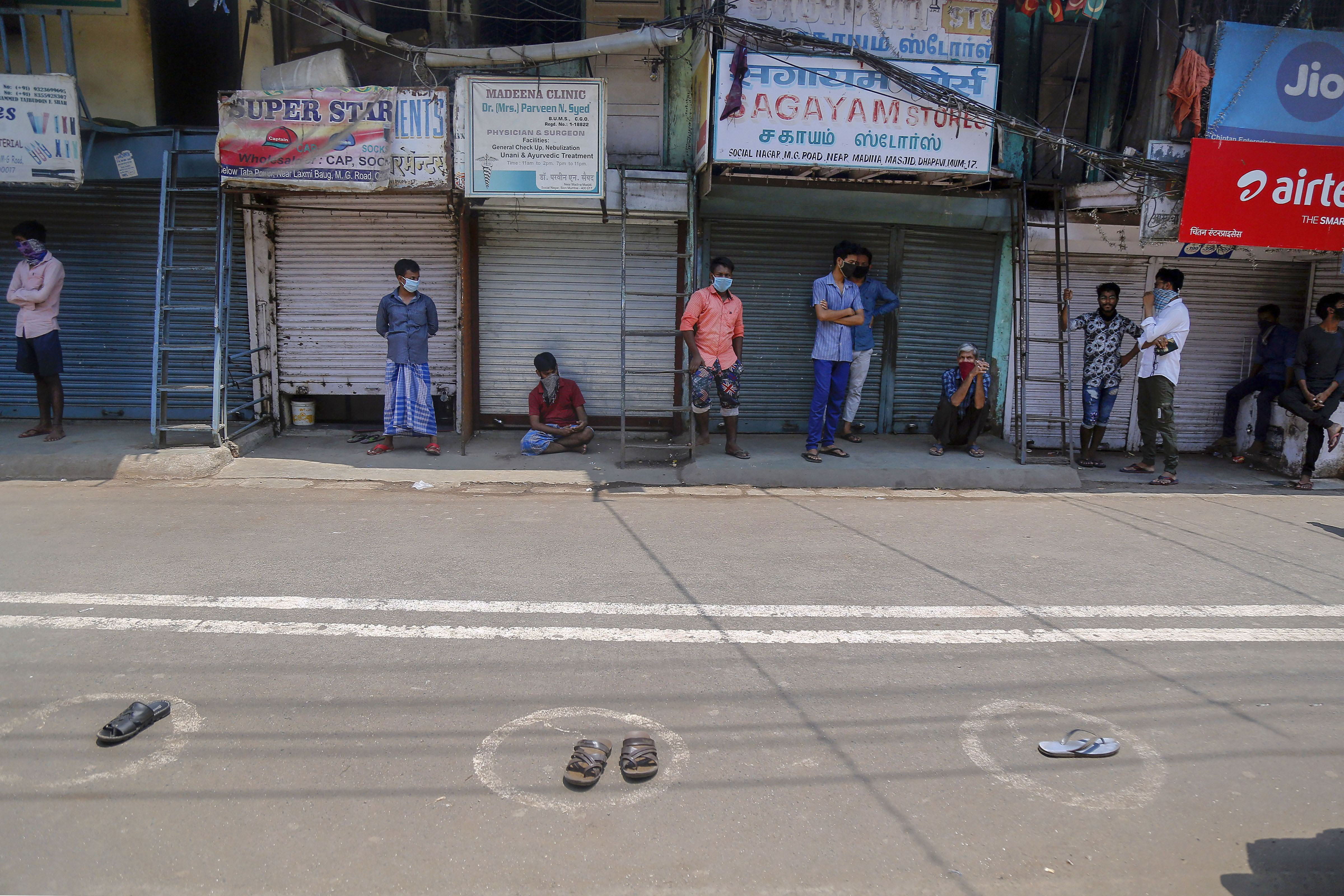 Migrant workers put their footwear in painted circles as they stand in shade to collect food during a nationwide lockdown in the wake of coronavirus pandemic, at Dharavi in Mumbai, Sunday, April 19, 2020.