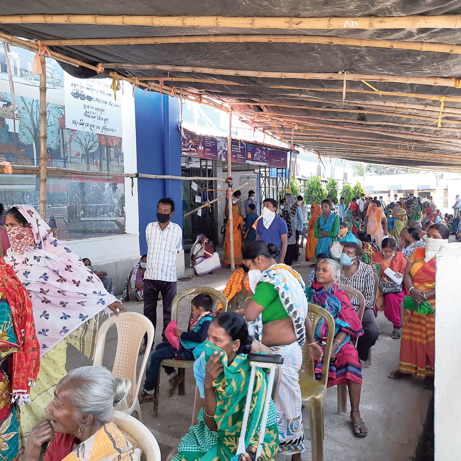 People queue up in front of a customer service point in Birbhum's Mallarpur on Friday