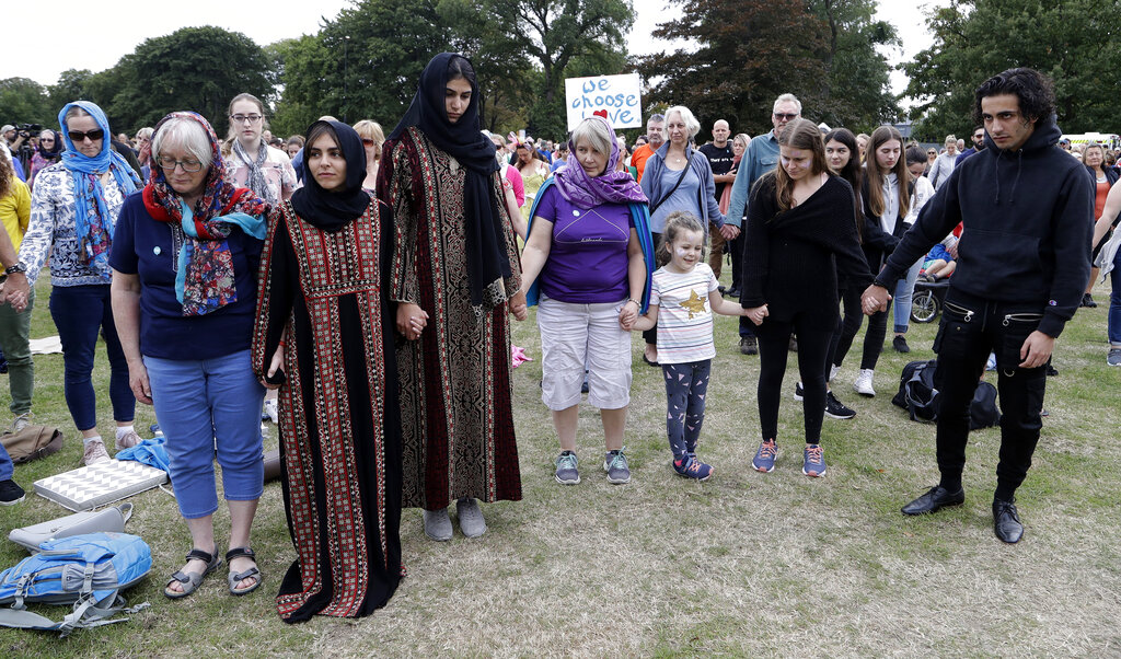 Students and members of the public hold hands during a minute's silence ahead of the March for Love following last week's mosque attacks in Christchurch, New Zealand, on Saturday.