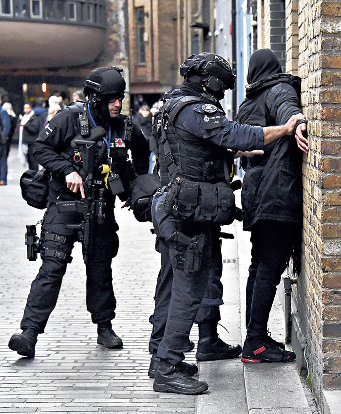 Police officers search a man on the south side of London Bridge on Friday
