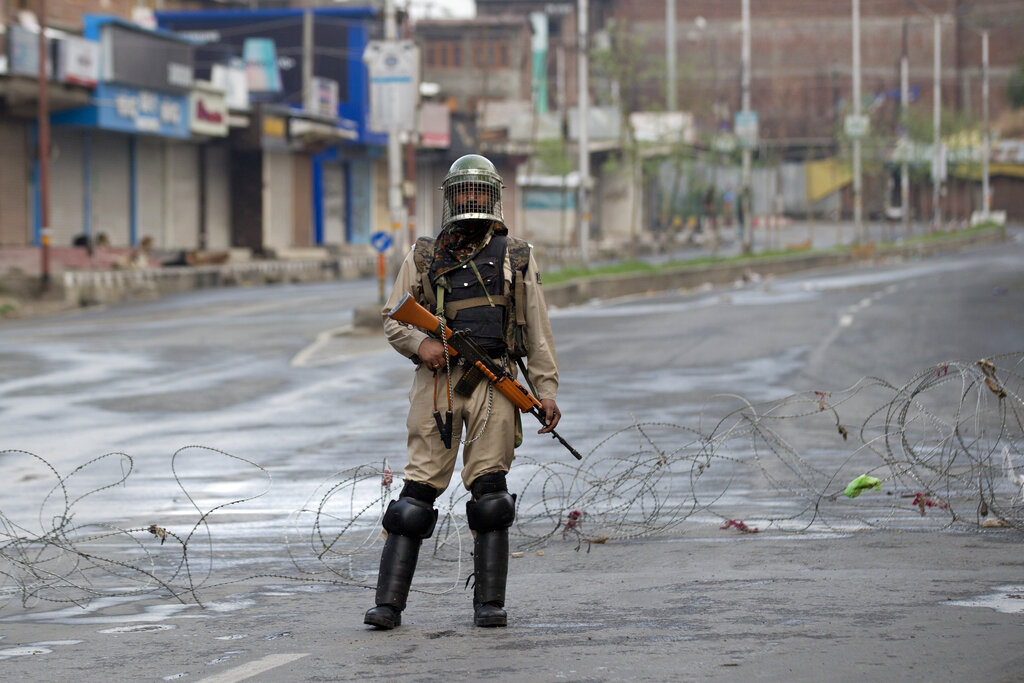 An Indian Paramilitary soldier stands guard on a deserted road during curfew in Srinagar on Wednesday, Aug. 7, 2019.