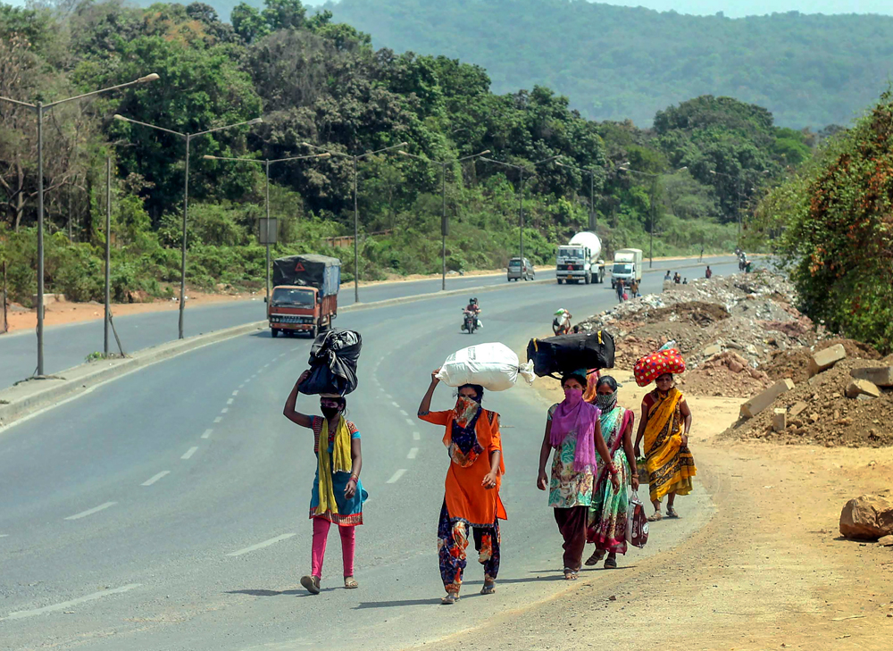 Migrant workers and their family members walk on the national highway to reach their native place in Jalgaon district of Maharashtra, during a nationwide lockdown, in the wake of coronavirus, in Mira Bhayandar area of Mumbai, Thursday, April 30, 2020.
