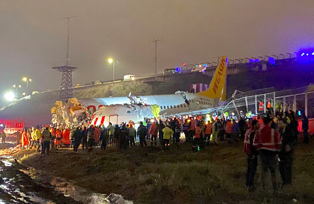 Rescue members and firefighters work after a plane skidded off the runway at Istanbul's Sabiha Gokcen Airport, Istanbul, Wednesday
