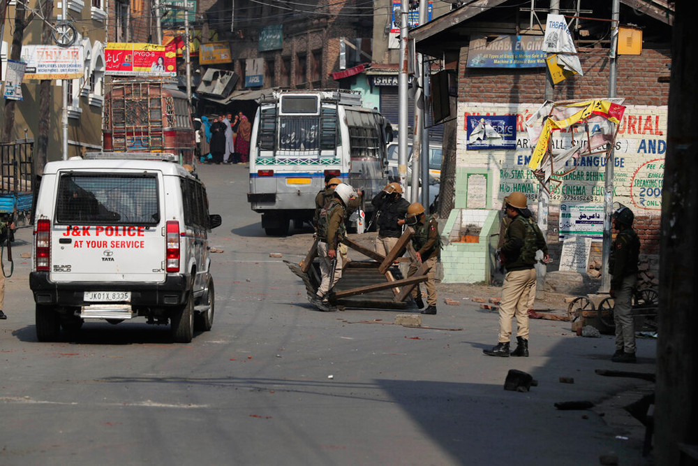 Policemen remove roadblocks put up by protesters in Srinagar on Tuesday