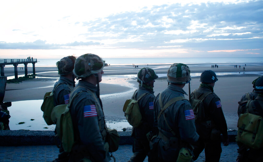 World War II re-enactors walk down to Omaha Beach, in Normandy, France, at dawn on Thursday, June 6, 2019 during commemorations of the 75th anniversary of D-Day.