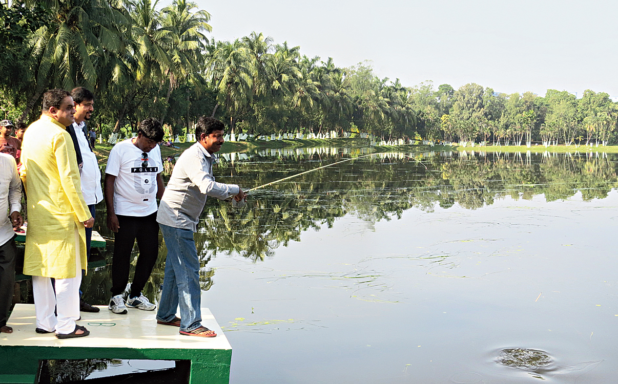 Ministers Bratya Basu and Sujit Bose watch a fish catch bait at Banabitan on Friday.