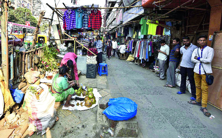 Vacuum filled: A woman sells green coconuts on the footpath along the Gariahat-bound flank from Ruby hospital, within 50ft of the junction, on Friday. The spot fell vacant after hawkers were removed from within 50ft of the intersection the day before.