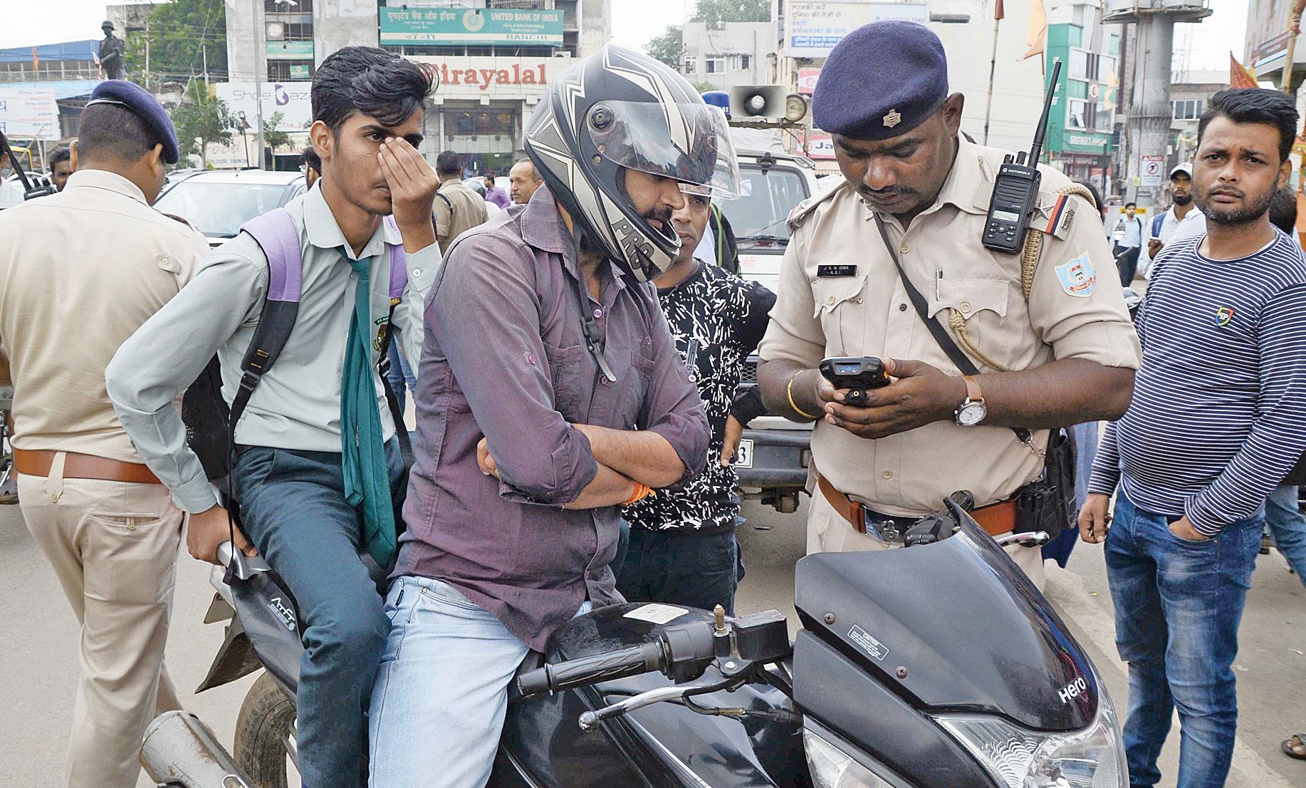 A traffic cop fines a biker with a helmet-less pillion rider at Albert Ekka Chowk in Ranchi on Thursday, September 5.