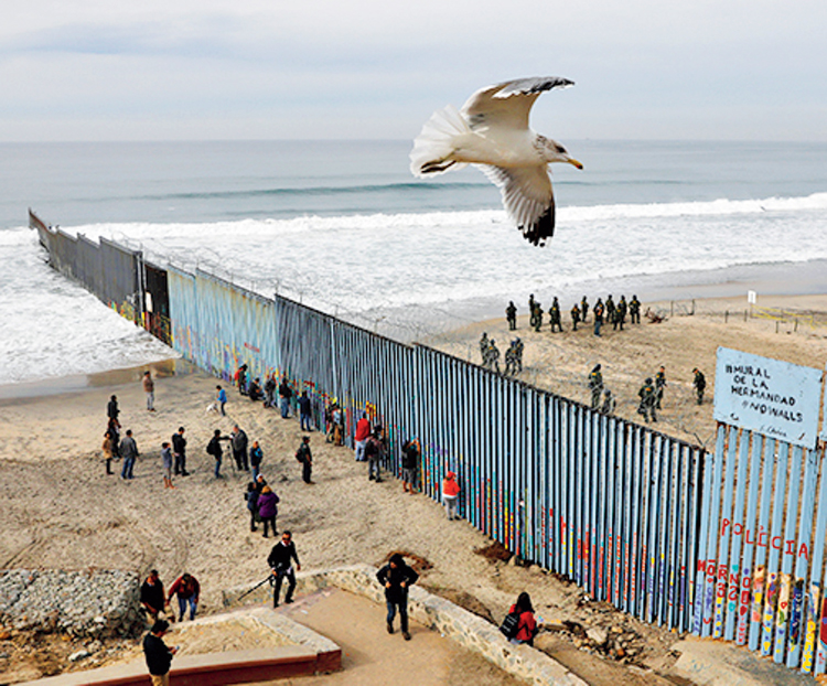 In this December 10, 2018, file photo, people look on from the Mexican side, left, as US.Border Patrol agents on the other side of the US border wall in San Diego prepare for the arrival of hundreds of pro-migration protestors, seen from Tijuana, Mexico.