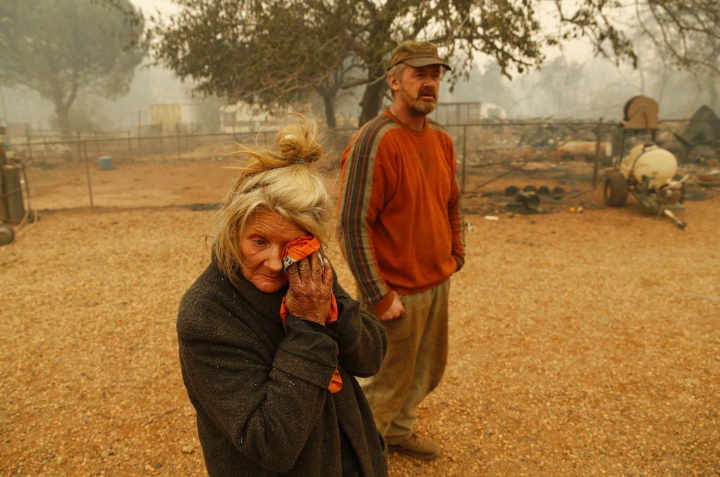 Cathy Fallon wipes her face as she and her son Gabriel stand near the charred remains of her home in Paradise on Friday.