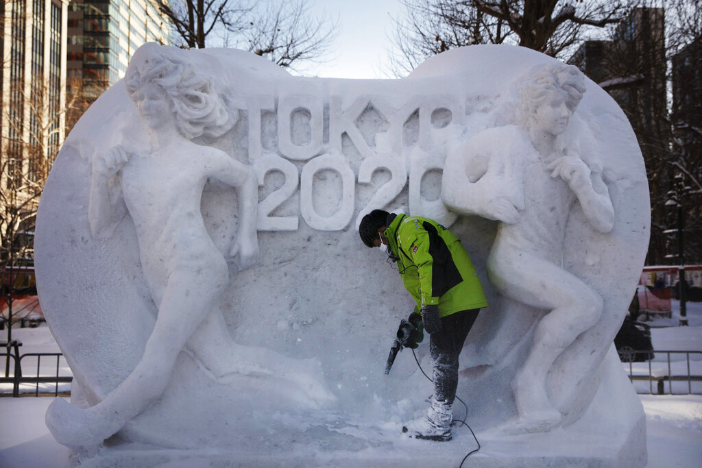A worker blows fresh snow off a snow sculpture celebrating Sapporo's hosting of Tokyo 2020's marathon and race walk during the Sapporo Snow Festival