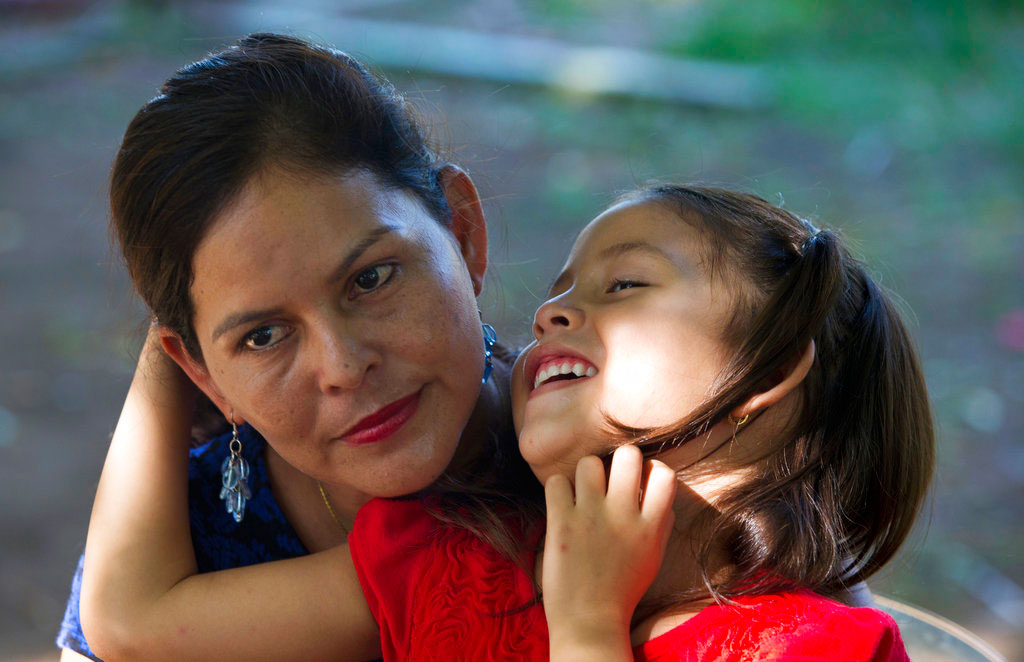 Araceli Ramos holds her daughter, Alexa, on her lap during an interview in a park in San Miguel, El Salvador.