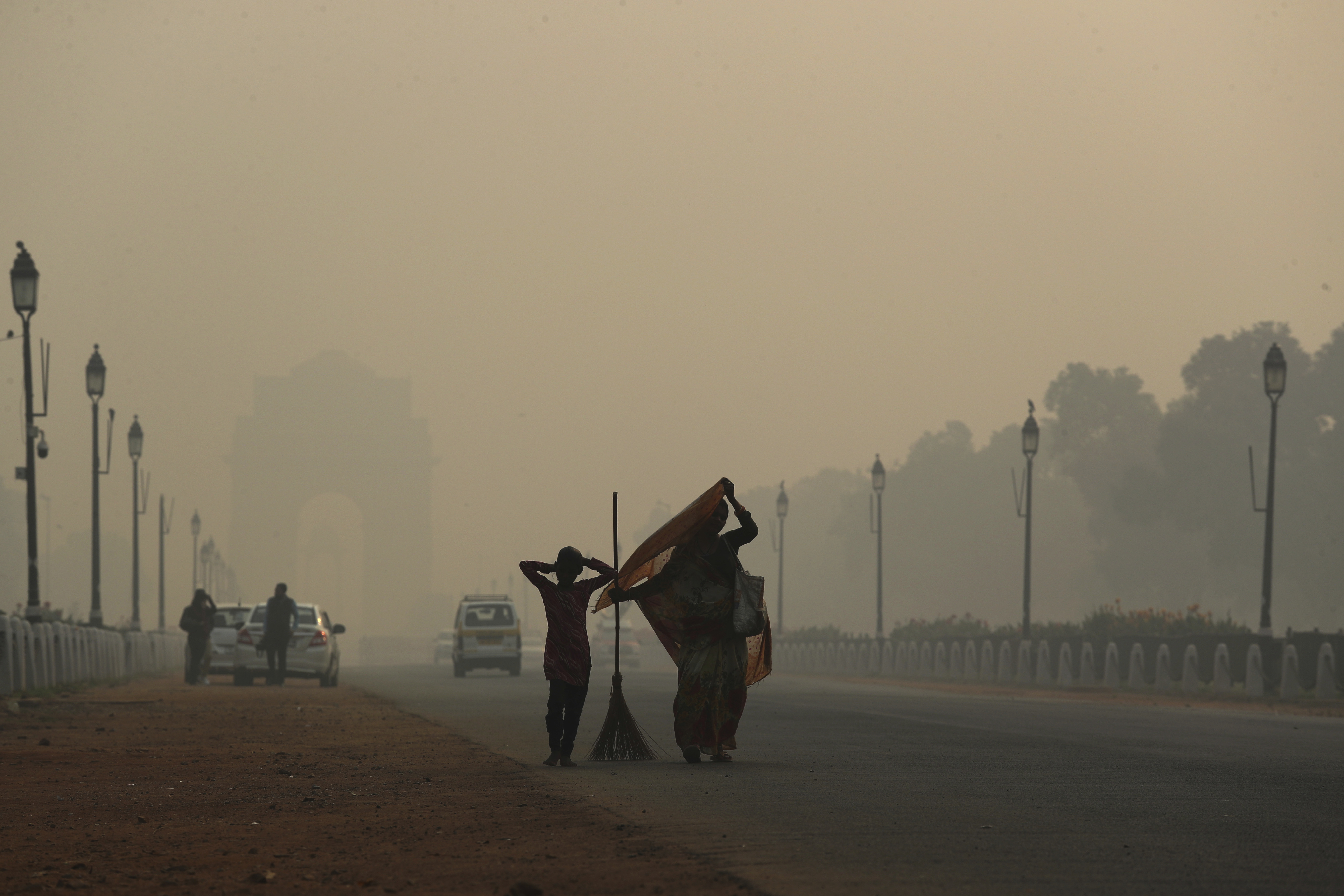 A municipal worker with her daughter leaves after sweeping the India Gate area in Delhi, on Thursday, November 8, as a thick haze of pollution hangs over the city the day after Diwali.