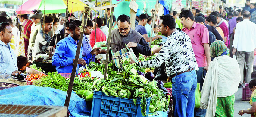 Residents buy vegetables at a market in Guwahati on Saturday during curfew relaxation
