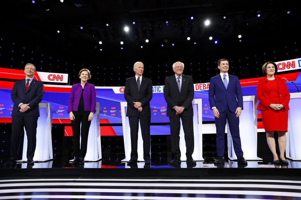 From left, Democratic presidential candidates businessman Tom Steyer, Sen. Elizabeth Warren, D-Mass., former Vice President Joe Biden, Sen. Bernie Sanders, I-Vt., former South Bend Mayor Pete Buttigieg, and Sen. Amy Klobuchar, D-Minn., stand on stage, Tuesday, Jan. 14, 2020, before a Democratic presidential primary debate hosted by CNN and the Des Moines Register in Des Moines, Iowa.