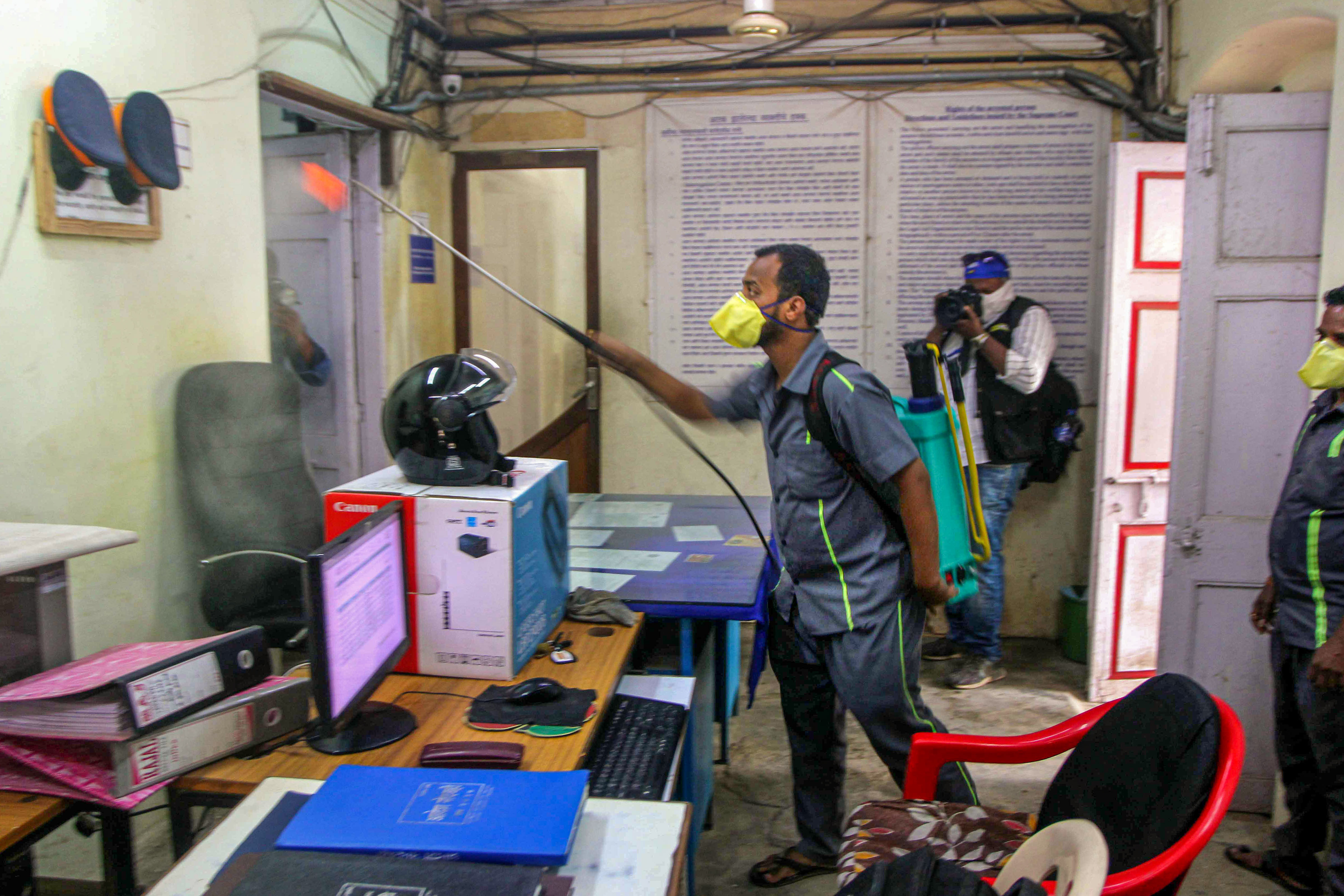An MCD worker sprays disinfectant inside Gorai Police Station during a nationwide lockdown, imposed in the wake of coronavirus pandemic in Mumbai, Saturday, March 28, 2020