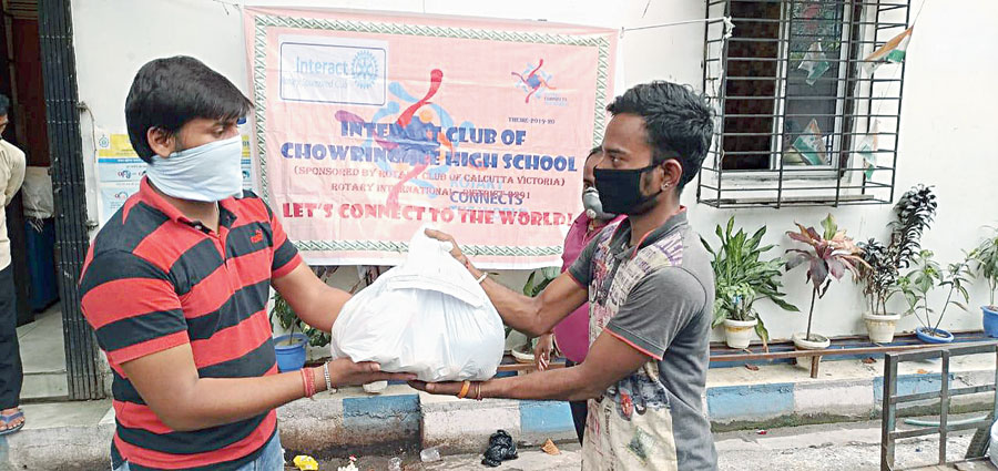 Students of Chowringhee High School distribute essential items like rice, potatoes and oil
