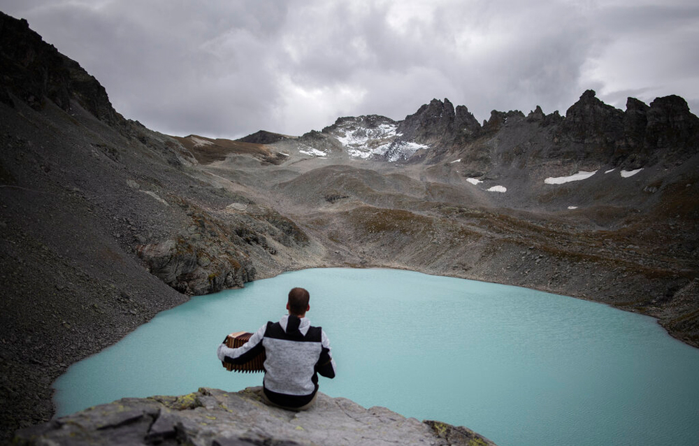 A hiker plays his accordion near the Wildlake and the Pizol glacier during a commemoration for the 'dying' glacier of Pizol mountain in Wangs, Switzerland, on Sunday