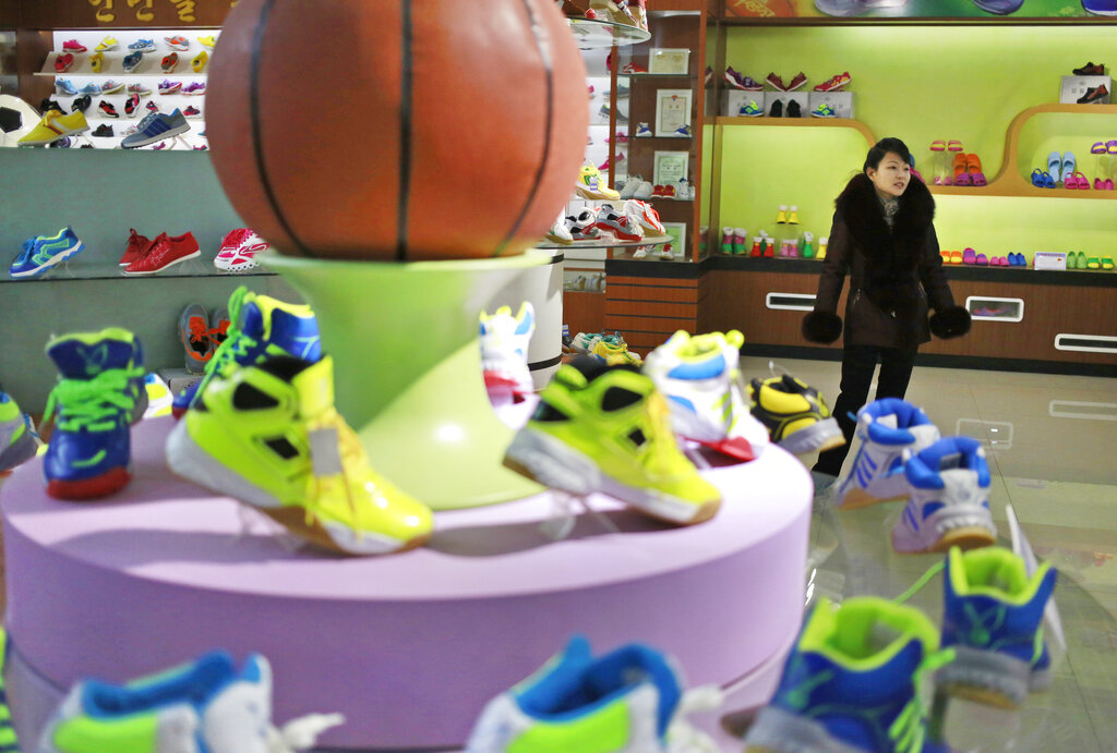 A guide stands near a basketball shoe display in a product exhibition room at the Ryuwon Shoe Factory that specialises in sports footwear, in Pyongyang.