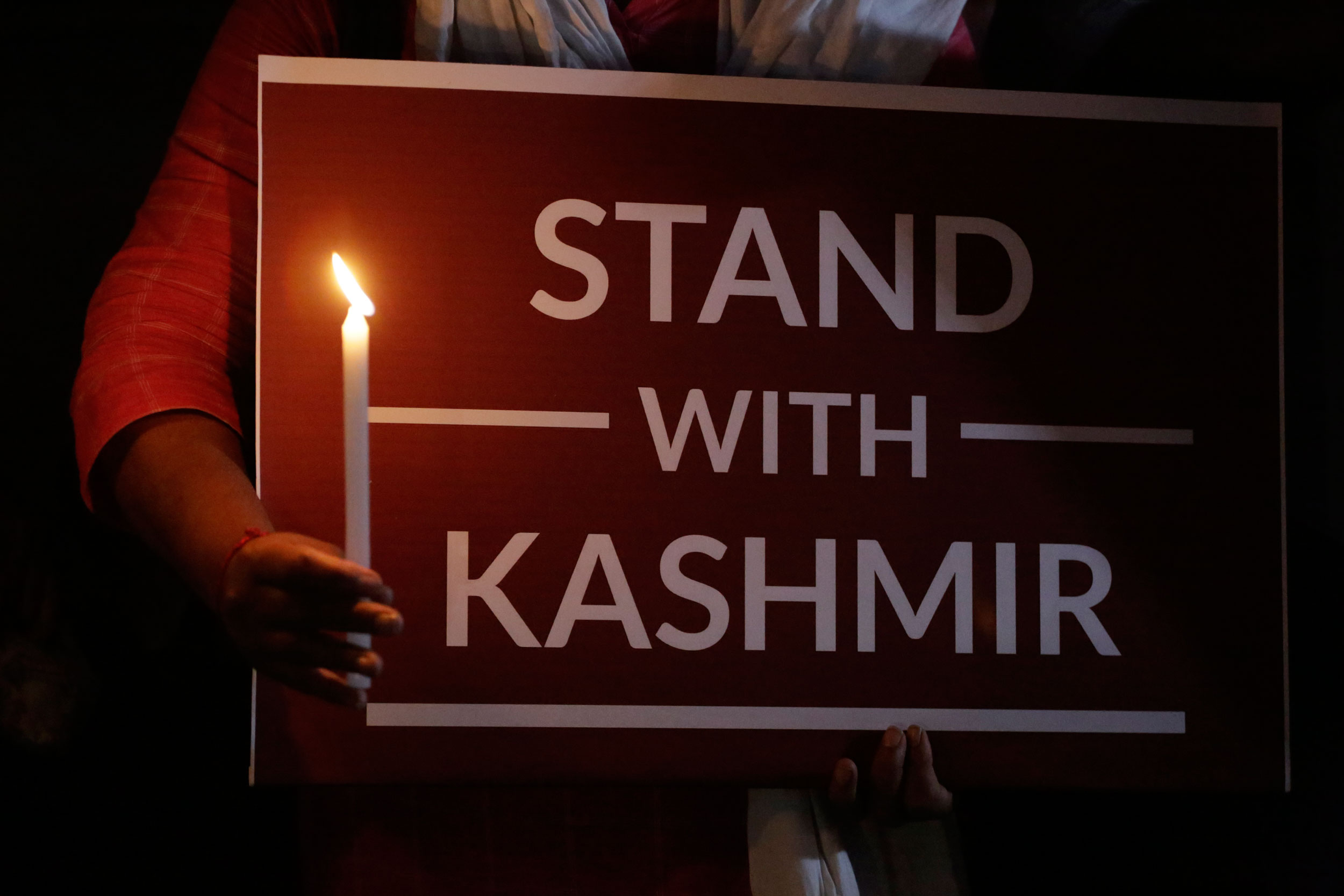A woman holds a candle and a placard expressing solidarity with the citizens of Kashmir during a candle light vigil in Ahmadabad on October 17, 2019.