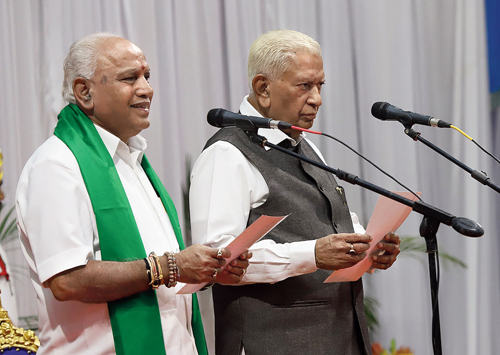 BJP leader BS Yediyurappa (left) being sworn in as chief minister of Karnataka in July after the 17 MLAs defected from the Congress and the JDS