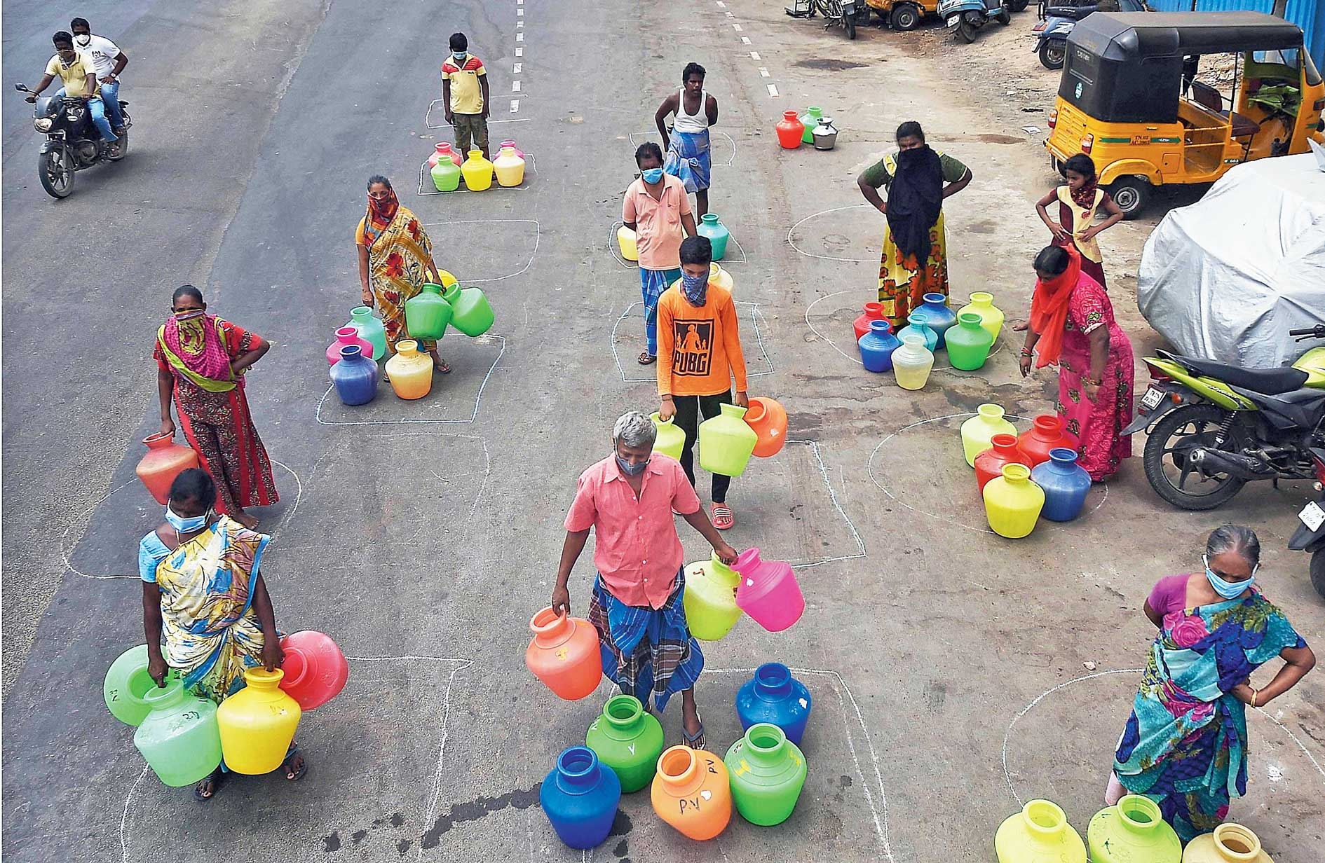 People maintain social distance as they stand in queues to collect drinking water in Chennai on April 7, Tuesday, during the lockdown.