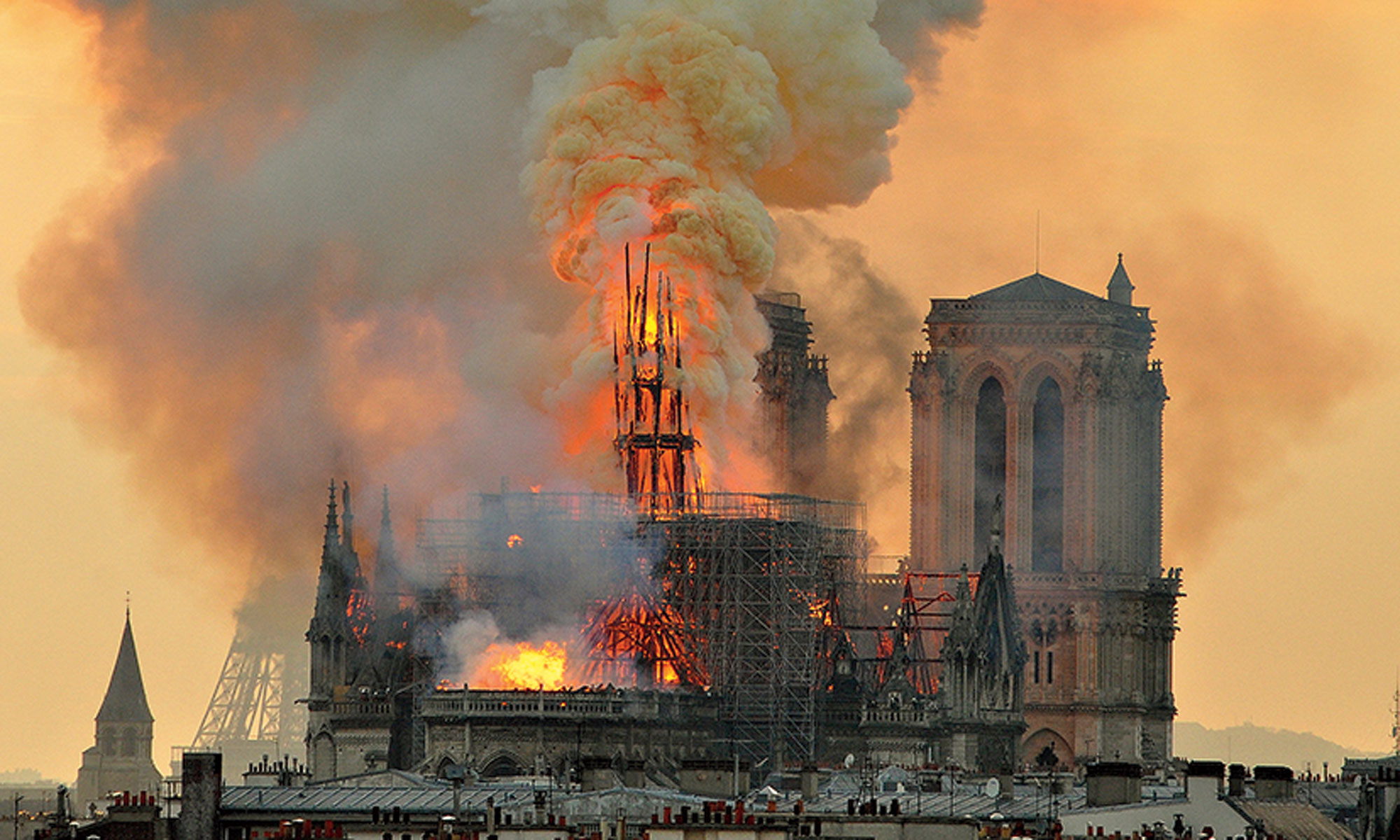 In this image made available on Tuesday, April 16, 2019, flames and smoke rise from the blaze after the spired toppled over on Notre Dame cathedral in Paris on Monday, April 15, 2019.