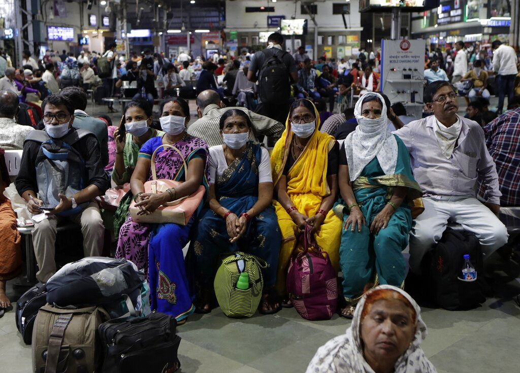 People wait at a train station wearing protective masks as a precaution against the coronavirus outbreak in Mumbai, Tuesday, March 17, 2020.