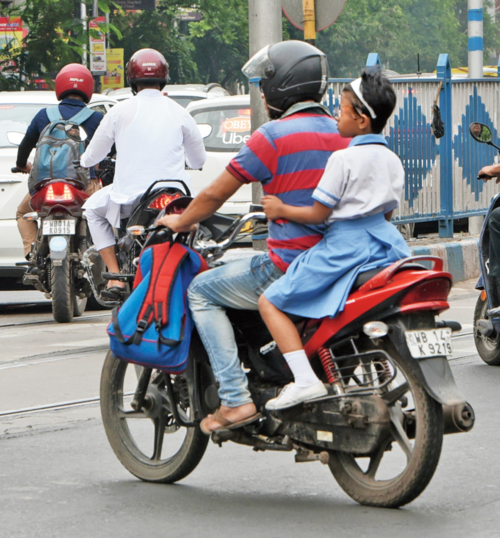 A man rides a bike with a girl on the pillion without a helmet near Modern High School for Girls