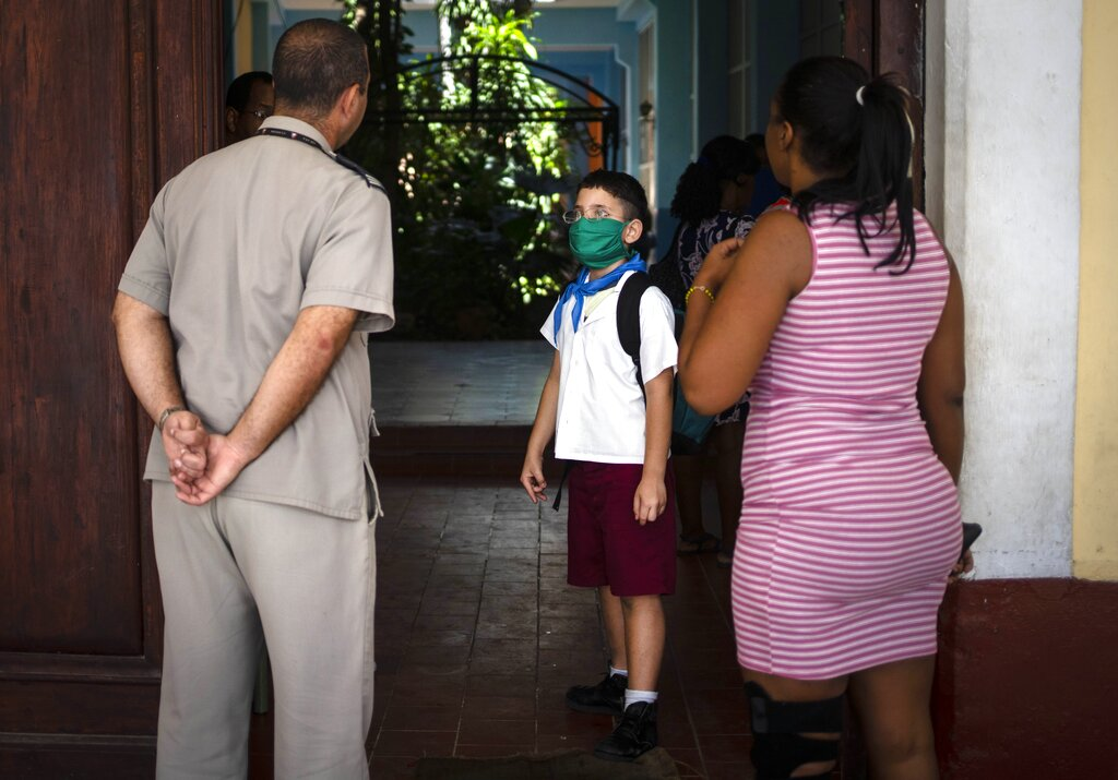A student wearing a mask as a precaution against the spread of the new coronavirus waits at the school gate to be picked up by his father at the end of the school day in Havana, Cuba, Friday, March 20, 2020.