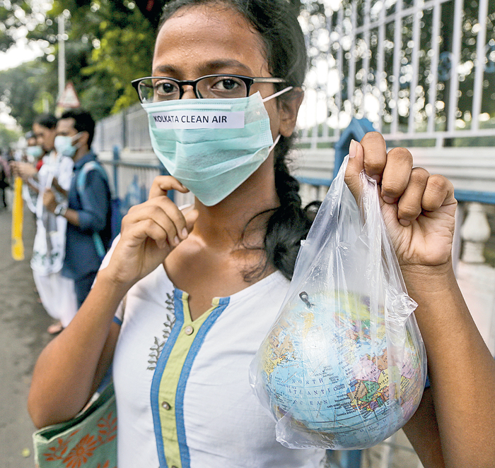 A woman holds a globe in a plastic bag during climate protests in Calcutta