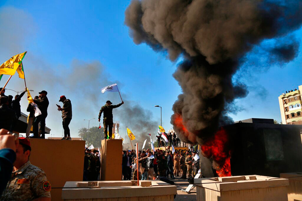 Protesters set fires in front of the US embassy compound, in Baghdad, Iraq, on December 31, 2019.