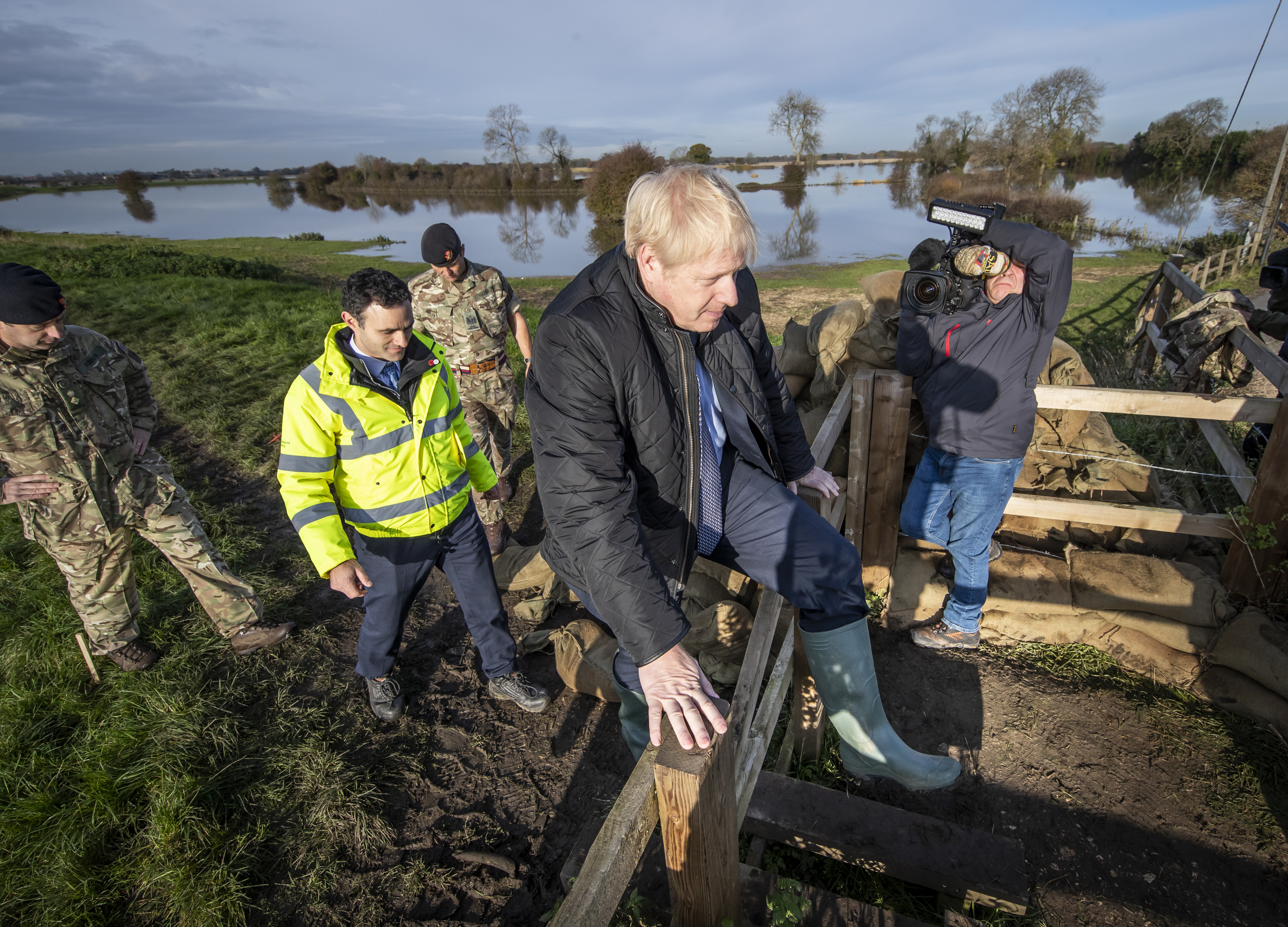 Boris Johnson, clambers over a fence, during a visit to see the effects of recent flooding, in Stainforth, England, Wednesday, November 13, 2019