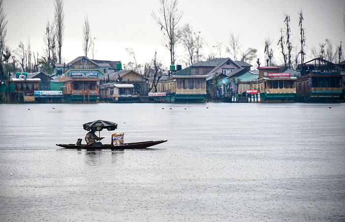 A vendor rows his boat on the Dal Lake amid rain on Wednesday