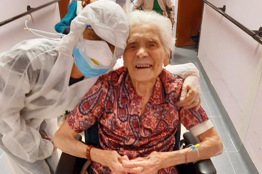 In this photo taken on April 1, 2020, 103-year-old Ada Zanusso, poses with a nurse at the old people's home